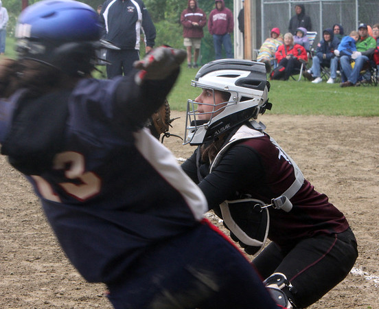 ALLEGRA BOVERMAN/Staff photo. Gloucester Daily Times. Rockport: Rockport's Mollie Watson, right, prepares for the ball as North Shore Tech's Holly Ryan flies through home plate on Sunday during their game in Rockport.
