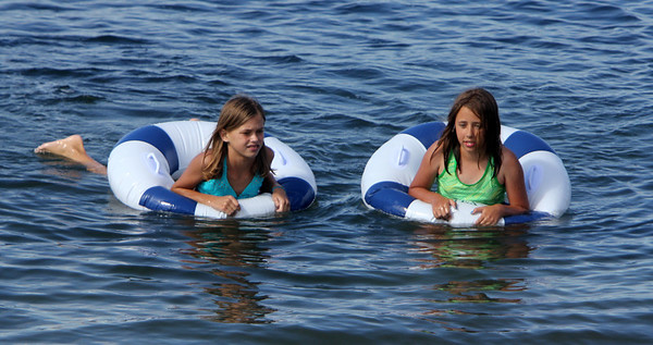 ALLEGRA BOVERMAN/Staff photo. Gloucester Daily Times. Rockport: Alina Lorigan, 10, left, of Jupiter, Fla., and her summer friend Clara Collins, 10, of Rockport, float together in identical blue and white inner tubes in the water off Old Garden Beach on Thursday afternoon. Alina spends most of the summer each year in Rockport spending time and having adventures with her grandparents, who live there.