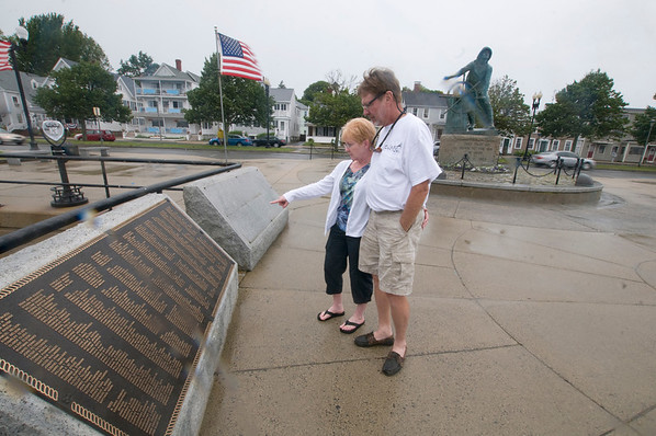 Gloucester: Cindy and Sam Stewart read the names on the plaques at the Fisherman's Memorial in the rain Monday afternoon. Names are being added to the final plaque of those resently lost to the sea. Jim Vaiknoras/staff photo