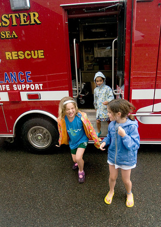 Manchester: Annabel Smith, Martha Davis and her sister Hannah  come laughing out of an ambulance they were checking out during Truck Night in Town Hall Parking Lot in Manchester Tuesday night. The rainy evening gave residence an opportunity to check out Police, Fire and DPW vehicles and meet the people who use them. jim Vaiknoras/staff photo