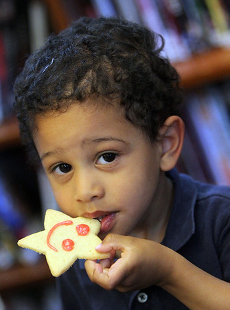 ALLEGRA BOVERMAN/Staff photo. Gloucester Daily Times. Manchester: Alexander Massillon, 2, takes a bite of a butter cookie decorated by his sister Cosima Massillon, 9, at the Manchester Public Library during the  young adult summer reading program kickoff party on Thursday afternoon.
