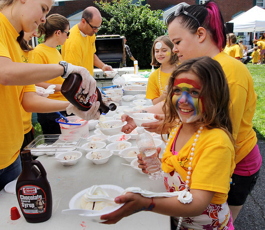 ALLEGRA BOVERMAN/Staff photo. Gloucester Daily Times. Gloucester: Caisha Lorentzen, 9, front, reacts to having whipped cream sprayed onto her arm by Jen Perry, the nutrition development coordinator for The Open Door, during the Open Door Food Pantry Summer Lunch program held at Riverdale Park on Veterans Way on Friday afternoon. Behind her is Brandy Norris.