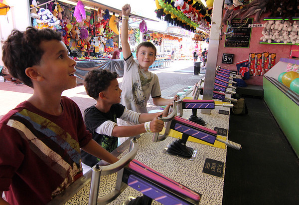 ALLEGRA BOVERMAN/Staff photo. Gloucester Daily Times. Gloucester: From left, Dagne and his twin brother Gregorio Auditore, 8, and their friend Griffin Noele, 8, all of Rockport, try their luck in the Water Gun Fun booth at the carnival at Fiesta on Friday afternoon.
