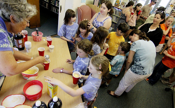 ALLEGRA BOVERMAN/Staff photo. Gloucester Daily Times. Essex: During the Annual Root Beer Float Day at the T.O.H.P. Library in Essex sponsored by the Friends of the Library,Bonnie Bradford, left, a member of the Friends of the Library, and Beth Cairns, a library trustee, made at least 175 root beer floats for people.
