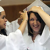 ALLEGRA BOVERMAN/Staff photo. Gloucester Daily Times. Rockport: Emily Good, left, helps Kimberly Rogers with her cap before Rockport High School commencement at the school on Friday evening. Good will be attending Northeastern in the fall for English and Rogers will attend Fitchburg State for nursing.