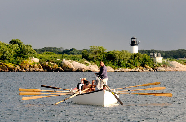 Gloucester: One of the crews waits for their heat to start at the Seine boat eliminations on Pavilion Beach Wednesday night. with the Ten Pound Island lighthouse behind Jim Vaiknoras/staff photo