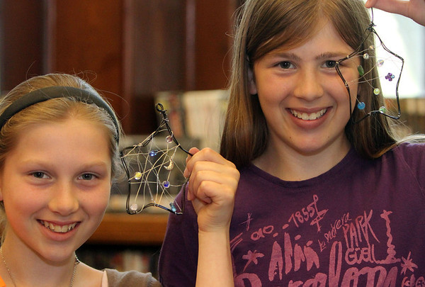 """ALLEGRA BOVERMAN/Staff photo. Gloucester Daily Times. Manchester: Tori Potter, left, 11, and her sister Julia Potter, 13, show of their glow-in-the-dark moon catchers they made during the Manchester Public Library's Young Adult Summer Reading Program, """"Own The Night,"""" kickoff party on Thursday afternoon.  They were among about 25 participants and they also decorated star-shaped butter cookies and entered a raffle."""