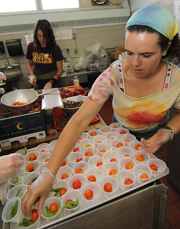 "ALLEGRA BOVERMAN/Staff photo. Gloucester Daily Times. Gloucester: During the ""Rainbow Warrior"" day at Veterans Memorial  Elementary School on Thursday, students sampled fruits and vegetables in a rainbow of colors and then charted their reaction to their taste, texture, crunch, juiciness and other criteria. Produce included grapes, peaches, cherry tomatoes and snow peas. The activity was part of the FoodCorps and CitySprouts food-related events that have been taking place all year at the school. Preparing more samples for students are, front, Erin Taylor placing tomatoes and in back, Grace Cherubino, slicing peaches."