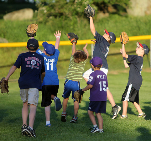 Allegra Boverman/Staff photographer. Gloucester Daily Times. Gloucester: Little League players rush to catch a ball during the home run derby during the Seventh Annual Gloucester Little League Family Picnic and Skills night held at Boudreau Field on Friday evening.
