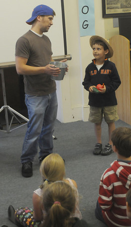 Essex: Greg Nikitas gets some help from Brian Kelly during the  Great Big Planet presentation at the Essex Library Tuesday night.  Nikitas used tale of the Old West and stories of about farming to give a message about conservation and taking care of the planet. JIm Vaiknoras/staff photo
