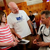 ALLEGRA BOVERMAN/Staff photo. Gloucester Daily Times. Gloucester: U.S. Sen. Scott Brown, right, signs a photo for Molly McAreavey of Gloucester, left, and her dad, Jack, during Brown's visit to Lobsta Land in Gloucester on Saturday.