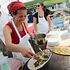 ALLEGRA BOVERMAN/Staff photo. Gloucester Daily Times. Gloucester: Mahroussie Jabba of Gloucester, front, prepares various Lebanese breads to be baked on a saj, during the opening day of the Cape Ann Farmers Market held in Stage Fort Park on Thursday afternoon. Around her from left are her husband Richard Jabba, and neice Erica Dollof.