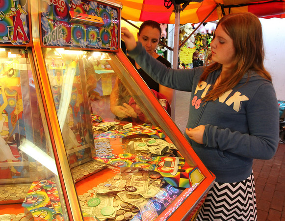 MARIAUMINSKI/GLOUCESTER DAILY TIMES Moriana Rowe, 12 of Gloucester, puts her money into the car wash game for another round at the St. Peter's Fiesta Carnival.