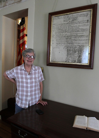 MARIA UMINSKI/GLOUCESTER DAILY TIMES Rev. Wendy Fitting stands next to the Unitarian Universalists Church's charter in the Historical Room of the Unitarian Universalists Church in Gloucester. Rev. Wendy is retiring after 24 years of pastoring the church.
