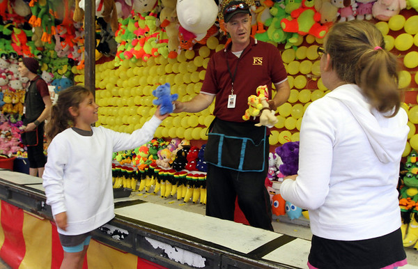 MARIAUMINSKI/GLOUCESTER DAILY TIMES Caicha Lorentzen, 10 of Gloucester, and Chanel Richards, 9 of Rockport, pick out their prizes after playing at darts game at the St. Peter's Fiesta Carnival on Thursday night.