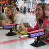 MARIAUMINSKI/GLOUCESTER DAILY TIMES From right to left, Heather Dagle of Gloucester, pulls double duty helping both daughters Sofia Dullea, 2, and Claire, 3, race Robin Towne of Gloucester, and her son James, 3, at the Water Race game during St. Peter's Fiesta Carnival on Thursday Night.