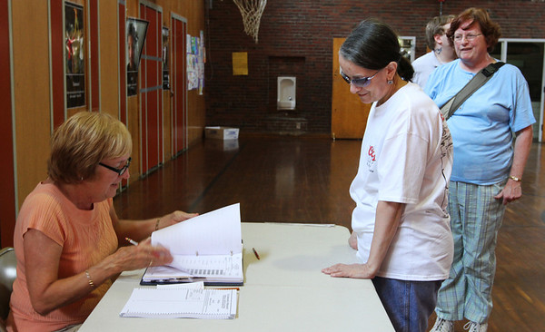 MARIAUMINSKI/GLOUCESTER DAILY TIMES Poll worker Janet Robbins checks in local voter Theresa Mortillaro at Beeman Elementary School in Gloucester on Tuesday June 25 so Mortillaro could cast her ballot in the Massachusetts US Senate race.