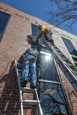 Desi Smith /Gloucester Daily Times.  Anthony Saputo (top) and Andy Orlando of Seaside Glass and Mirror in Gloucester, clean the new windows they instaled as part of the on going work being done at the Cape Ann Savings Bank, Wednesday morning on the Roger St side.<br />    March 19,2014.