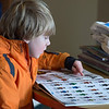 Desi Smith /Gloucester Daily Times.   Jack Bediz 6, of Essex, looks over some lego figures in a book Saturday morning at the Essex Public Library. Jack found the batman one he was looking for.<br />   March 1,2014.
