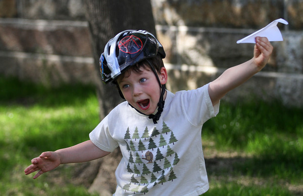 MIKE SPRINGER/Staff photo<br /> Five-year-old Eli Porter tests the aerodynamics of his paper airplane Monday during the Manchester Public Library's 4th annual paper airplane contest Monday on the library lawn. Kids made their own planes from an assortment of designs and competed against each other for distance and height.