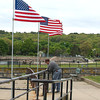 DESI SMITH/Staff photo.   Ringo Tarr, sets the last of the 85 flags just before crossing over the Blynman Bridge, shy of the 200 flags that line Stacy Boulavard from the Tavern to Stage Fort Park on Friday morning. <br />  May 23,2014
