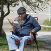"DESI SMITH/Staff photo.      84 old Ronald Joseph retired military,smokes his cigar and reads ""Death of the U-Boats Thursday morning outside his home at Pirates Lane. May 8,2014"