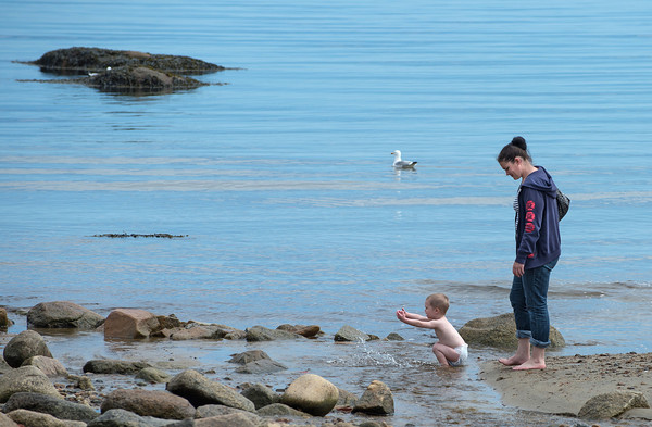 DESI SMITH/Staff photo.    Jennifer Murray of Rockport, stands close by as her son Caleb 2, plays with the water at the shores edge on Front Beach Thursday morning in Rockport.  May 8,2014