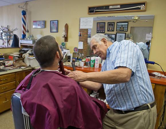 DESI SMITH/Staff photo.   Barber Joe Lucido cuts his grandson Kyle Lucido hair at his shop on Washington Street.  May 29,2014