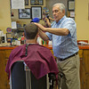 DESI SMITH/Staff photo.   Barber Joe Lucido cuts his grandson Kyle Lucido hair at his shop on Washington Street.  May 29,2014