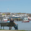 DESI SMITH/Staff photo.   Douglass and Marsi Walker of Gloucester, rest on a bench and to take in the veiws of the harbor and the city skyline on Rocky Neck Ave Thursday morning  while out for a walk.   May 8,2014