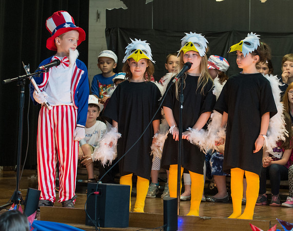 "DESI SMITH/Staff photo. Uncle Sam Charles Rousmaniere, listen as Rose Groleau, Beatrix Brosnihan and Emily Nelson, speak about the meaning of the eagle, in musical play, ""American Symbols,"" performed by all the first graders at West Parish School on Friday morning.<br />  May 23,2014"