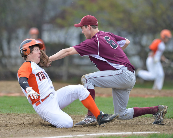 DESI SMITH/Staff photo.  Ipswich's #9 Sean Whooley takes a glove and ball to the face from Rockport's third basemen Conor Kuykendall, he trys to slide into thrid Saturday morning at Mile Lane Park in Ipswich. May 10 ,2014