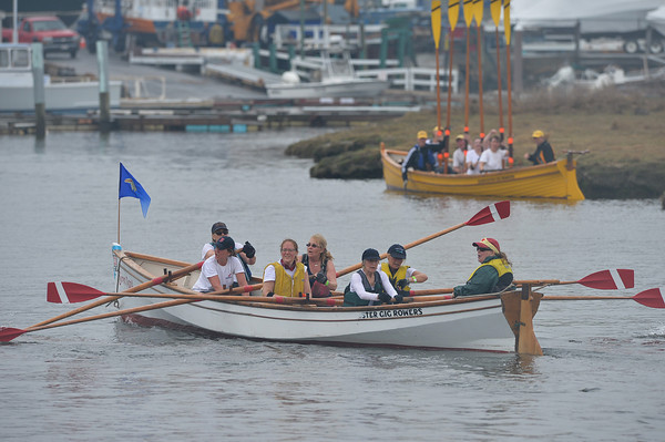 DESI SMITH/Staff photo.  Gloucester Gig Rowers raise their oars as other team members cross the finish in the Essex River Race, a 5.5-plus mile open water event that loops behind the barrier beaches of Ipswich and back through one of the most scenic tidal areas in New England, Saturday morning in Essex.   May 10,2014