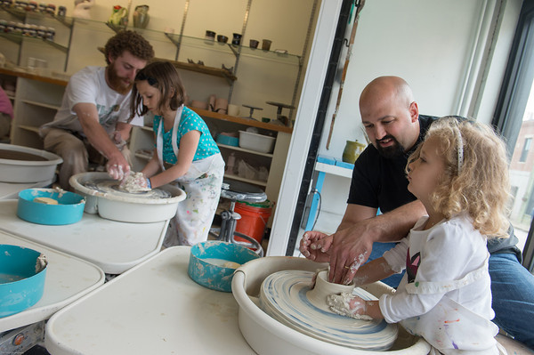 DESI SMITH/Staff photo.    David Brooks director of the Hive, (far left) helps Sophia Loiacano 7, of Gloucester, with some clay on the potters wheel, while her dad Bill Loiacono helps her sister Bianca 3, with her art piece Saturday afternoon in the Gloucester schools arts festival, were diffferent activites were held, at the Hive,City Hall and the Sawyer Free Library.   May 10,2014