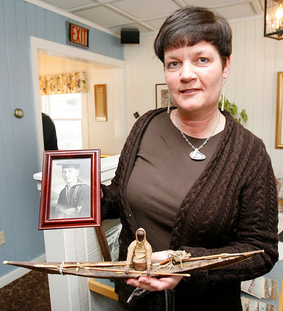 Essex: Jill Josephson of Gloucester displays a Greenland paddler made of seal skin, wood, and ivory that was appraised between $2-3,000 during Essex Antique night at Periwinkles. Josephson's grandfather brought the paddler home from his travels during World War II. Photo by Kate Glass/Gloucester Daily Times Thursday, March 19, 2009