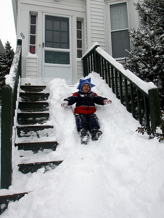 Gloucester: Benjamin Twalipo, 3, closes his eyes as he slides down the front steps of his aunt's home on Prospect Street yesterday afternoon. Twalipo also seemed to think the best way to get rid of the snow was to eat it. Photo by Kate Glass/Gloucester Daily Times Monday, March 2, 2009