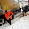 Gloucester: Gloucester Police Officer Tom Quinn, left, and Dave McGrath shovel sand under the tires of an 18-wheeler that got stuck at the intersection of Elm and Prospect Streets yesterday afternoon. The truck blocked traffic for approximately half an hour. Photo by Kate Glass/Gloucester Daily Times Monday, March 2, 2009