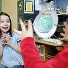 Essex: Paige Marshall reacts with delight while watching the fish appear in the bowl as Faith Costello spins an optical allusion toy she made as the Essex elementary School Daisy's troop met on Thursday afternoon.  The project they worked on was puting a fish on one side of a paper plate and a fish bowl on the other and attaching elastic bands to the sides of the plates so that when the plates spun the fish looked as if it was in the bowl.  Mary Muckenhoupt/Gloucester Daily Times