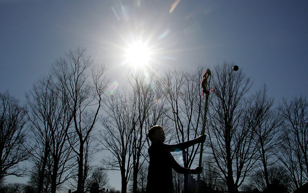 Manchester: Sam Creighton passes the ball to his friend while practicing lacrosse with his coach at Ed Field Field Saturday afternoon.  Mary Muckenhoupt/Gloucester Daily Times
