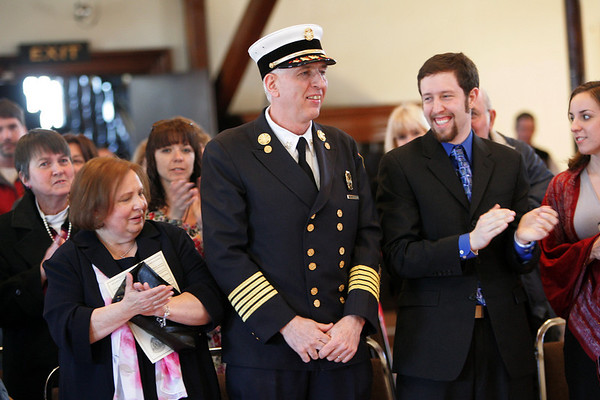 Gloucester: Fire Chief Barry McKay, standing next to his wife Diane and son Andrew, receives a standing ovation duirng his tribute to salute the chief held at Gloucester City Hall Wednesday afternoon. Mckay officially retires at the end of the month after 35 years with the Gloucester Fire Department. Mary Muckenhoupt/Gloucester Daily Times