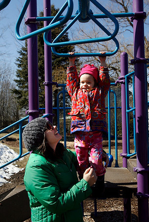 Gloucester: Colleen Apostolos-Marsh of East Gloucester holds her daughter, Lotus Marsh, 3, as she hangs from the monkey bars at Rebecca's Playground on Friday afternoon. Photo by Kate Glass/Gloucester Daily Times Friday, March 13, 2009