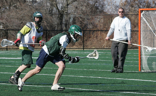 Manchester: Manchester Essex sophomore Will Curatolo runs the ball to the net while running drills with coach Nate Levie, right, during Lacrosse practice at Ed Field Field Friday afternoon. Mary Muckenhoupt/Gloucester Daily Times