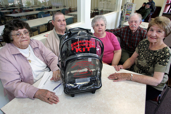 Gloucester: From left, Barbara Snare, Sam Randazza, his wife Mary Agnes, Peter Jenner and Phyllis Malone, members of the Gloucester Triad Council, sit with the new clear backpack to be used as an emergency kit for seniors at the Rose Baker Senior Center Thursday.  The Gloucester Triad Council in collaboration with the Council on Aging and the Gloucester Health Department has come up with this bag which will be sold to seniors for $5 and will be kept packed and ready to go for if an emergency strikes.Mary Muckenhoupt/Gloucester Daily Times