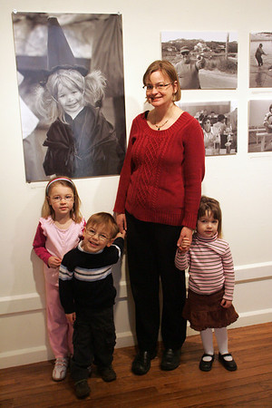 Gloucester: Jennifer Drost poses with her three children, from left, Julia, 5, and Erik and Anna, 3, in front of a photogrpah of Drost taken by Charlie Lowe when she was 2 years old at Halloween.  Drost took her children to the Cape Ann Museum for the Young at Art program which included a tour of the Lowe exhibit and an art project afterwards. Mary Muckenhoupt/Gloucester Daily Times