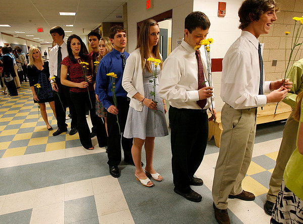Gloucester: Gloucester High School junior Jeff Lane smells the flowers that he and his fellow National Honor Society inductees will present to senior members during the Annual NHS Induction Ceremony last night. Photo by Kate Glass/Gloucester Daily Times Tuesday, March 31, 2009