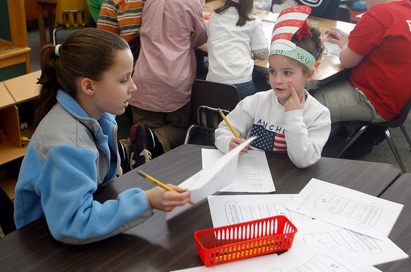 "Manchester: Lauren Coogan helps Emma Sanders think of words that end in -at as Manchester Memorial School commemorates the birthday of Dr. Seuss yesterday. Sixth graders visited kindergarten classrooms to play games inspired by one of Dr. Seuss' most famous books, ""The Cat in the Hat."" Photo by Kate Glass/Gloucester Daily Times Tuesday, February 3, 2009"