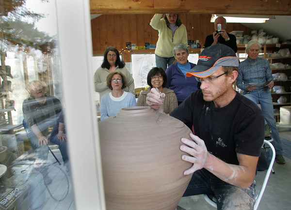 Rockport: Joe Christiansen, a potter from Minnesota, works on carving a fish in a two foot tall jar in Cynthia Curtis's pottery studio on Pigeon Hill Street as students and fellow potters look on Friday afternoon.  Christiansen is best known for making large pots that are four to six feet tall and will be Craft Boston at the Seaport World Trade Center this weekend. Mary Muckenhoupt/Gloucester Daily Times