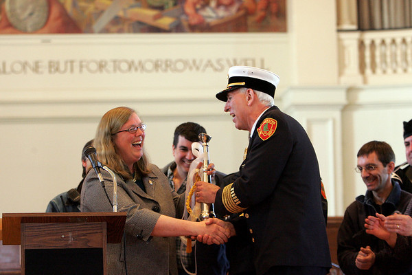 Gloucester: Fire Chief Barry McKay receives a silver speaking trumpet from Mayor Carolyn Kirk as a gift from the City of Gloucester during the tribute to Chief McKay held at Gloucester City Hall Wednesday afternoon.  Chief McKay officially retires at the end of this month.  McKay had also received an identical trumpet from the Gloucester Fire Department moments before. Mary Muckenhoupt/Gloucester Daily Times