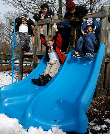 Manchester: Jack Hubbard, 6, Molly Karis, 8, and Drew Gross, 6, watch as Joey Purtell, 6, left, and Jack ten Hope, 6, go down the slide at Masconomo Park yesterday afternoon. The kids, and their moms, are all looking forward to spring. Photo by Kate Glass/Gloucester Daily Times Tuesday, March 10, 2009