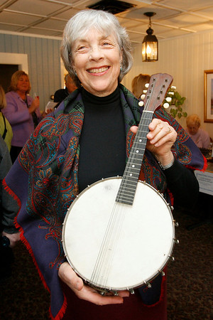 Essex: Louise Marsh of Gloucester displays an instrument from the 1890s that is a cross between a banjo and a mandolin that was appraised around $200 during Essex Antique night at Periwinkles. Photo by Kate Glass/Gloucester Daily Times Thursday, March 19, 2009